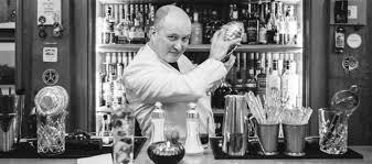 un barman préparant un cocktail derrière son bar