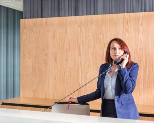 une réceptionniste vêtue d'un tailleur bleu, répondant au téléphone
