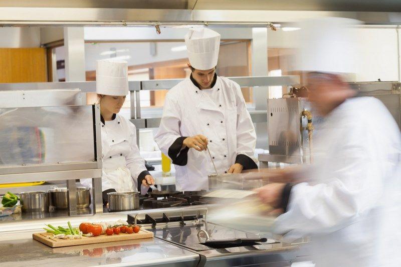 Brigade de cuisine préparant des plats dans les cuisines d'un restaurant