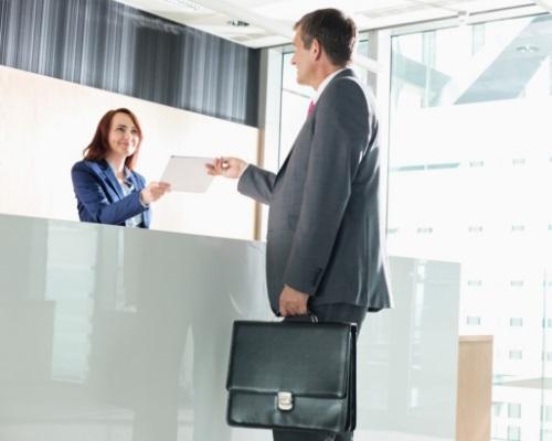 une réceptionniste accueil un client