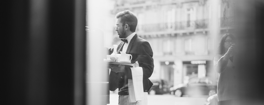 Cafetier portant un plateau serviette au bras
