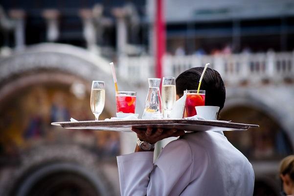 un serveur apporte un plateau sur lequel est disposé des boissons