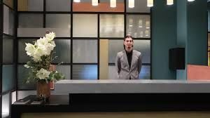 un homme debout face au comptoir de l'hôtel de nuit
