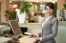 une femme vêtue d'un tailleur gris devant son écran d'ordinateur au comptoir d'un hôtel
